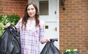 woman holding garbage bags