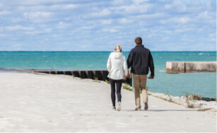 couple holding hands walking on pier